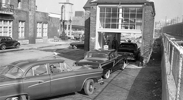 En 1956, le service des taxis de la Sûreté municipale inaugure la mise en service d'un « nouvel appareil ultra-moderne » afin de vérifier les taximètres ainsi que les odomètres des voitures de location. Dans son discours d'inauguration, Pacifique Plante, directeur intérimaire de la Sûreté municipale, déclare que cette installation est « probablement la première du genre en Amérique du Nord ». Photo: archive de Montréal.